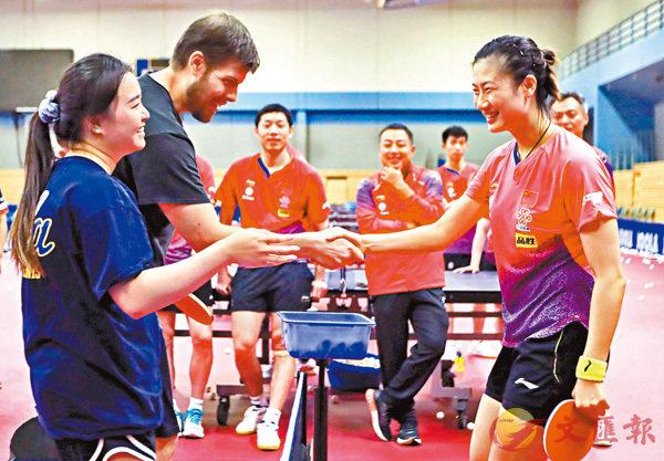■國乒「一姐」丁寧(右)與南加州大學球員握手致意。 新華社