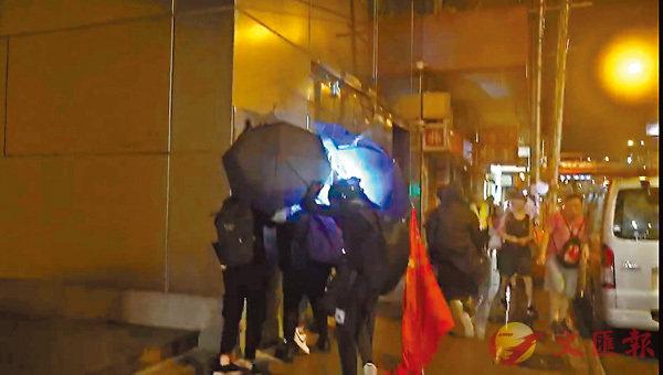 ■數名黑衣暴徒前晚把掛於粵海大廈外牆的國旗拆下,並丟棄地上。 資料圖片
