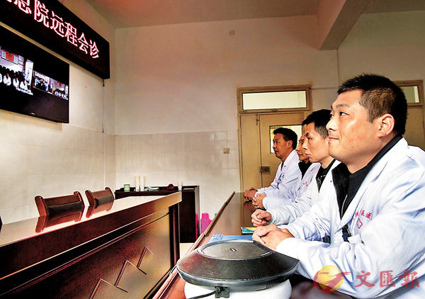 ■在陝西寧強中醫醫院巴山分院,董飛(右一)和同事們在遠程會診室同寧強縣中醫醫院專家會診病人病情。 資料圖片