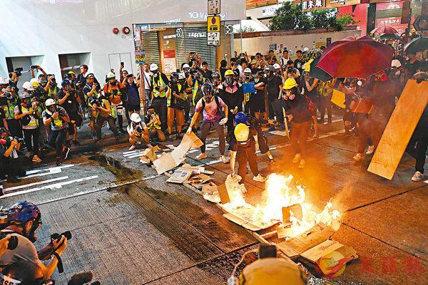 ■在暴徒街頭縱火現場,大批身穿反光衣的人聚集拍照,惟他們的記者身份真假難辨。 資料圖片