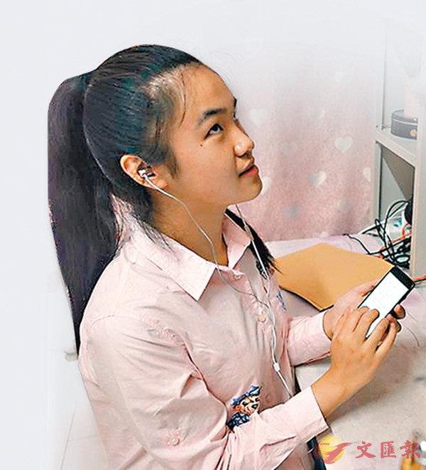 ■ 周文晴在南京特殊教育師範學院宿舍用手機「閱讀」文章。 新華社