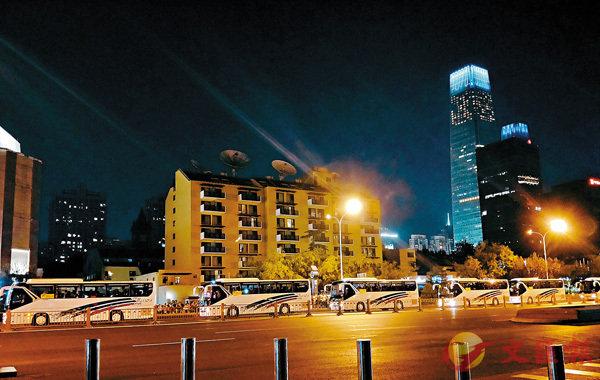 ■9輛大巴車依次通過永安里。 香港文匯報記者朱燁 攝