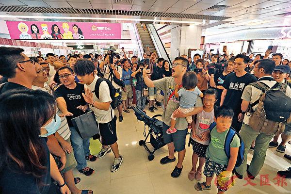 ■大批黑衣人在淘大商場公然唱「獨」歌,「正氣爸」疑看不過眼,手抱幼女激昂高唱國歌。香港文匯報記者  攝