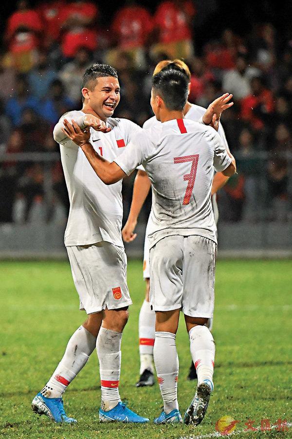 艾克森(左一)在武磊(左二)入球後慶祝。  新華社