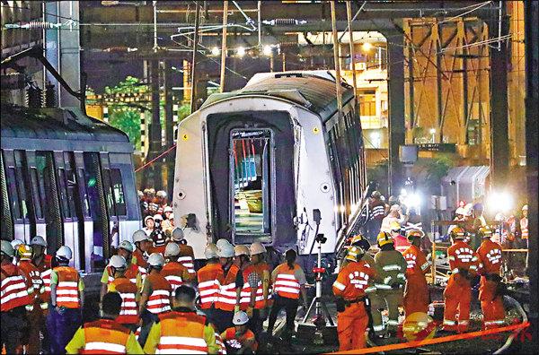 ■港鐵工程人員昨晚深夜挑燈夜戰,吊起出軌車廂。 香港文匯報記者  攝