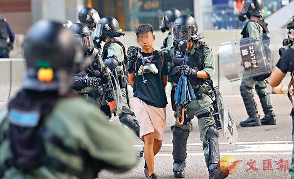■防暴警察在周日金鐘的驅散行動中拘捕一名男童。 香港文匯報記者  攝