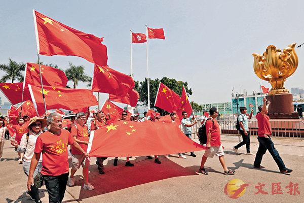 ■逾百市民昨日一早在金紫荊廣場揮舞國旗,慶祝新中國成立70周年。香港文匯報記者  攝