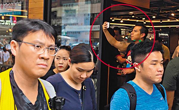 ■ 有拍照的路人被暴徒以鐳射槍照射(紅圈)。 香港文匯報記者  攝