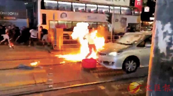 10月4日  ■黑衣魔在元朗大馬路向被打倒在地上的便衣警員投擲汽油彈。 資料圖片