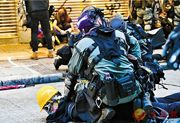 ■自實施禁蒙面法起3天內,77人涉嫌干犯新例被捕。圖為10月6日,警方在銅鑼灣拘捕其中一名戴上口罩蒙面的疑犯。   資料圖片