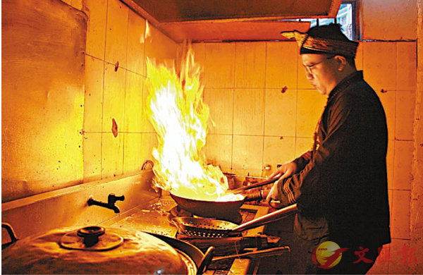 ■覃聰維正烹製毛南族美食。香港文匯報記者蘇征兵 攝