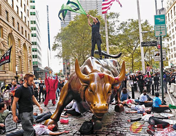 ■ 示威者在銅牛及自己身上潑上紅漆,再倒地扮死。  路透社