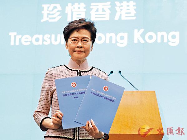 ■林鄭月娥昨日發表其任期內第三份施政報告。圖為林鄭月娥出席記者會向傳媒展示天藍色封面的《施政報告》及《附篇》。 香港文匯報記者  攝
