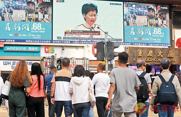 ■尖沙咀街頭大電視播放林鄭月娥宣讀施政報告,吸引市民關注。 香港文匯報記者  攝