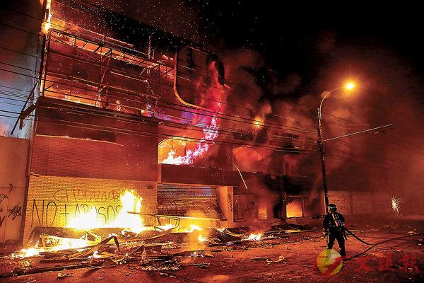■消防員向瓦爾帕萊索一間起火的超市灌救。路透社