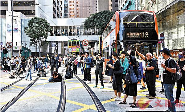 ■有人藉悼念周梓樂為名,堵塞中環德輔道中,後由警員搬走路障。 香港文匯報記者  攝