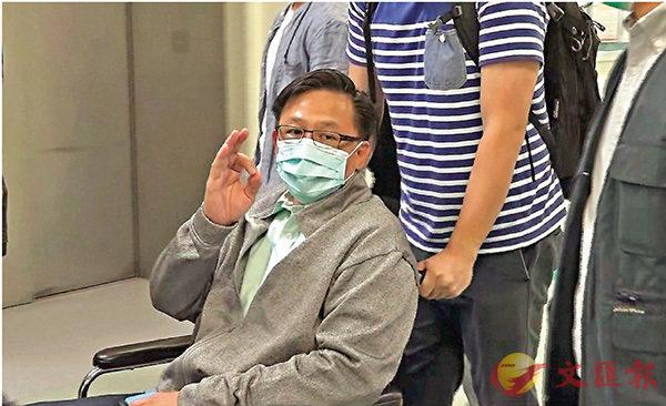 ■何君堯坐在輪椅上由友人推出病房。