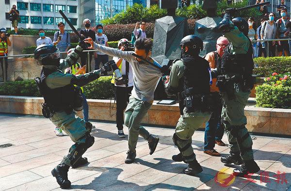 ■香港警察隊員佐級協會及香港消防主任協會均發表聲明,對暴徒的行為予以嚴厲譴責。圖為多名防暴警察昨日在中環合力制服滋事暴徒。 路透社