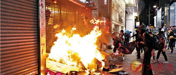 ■多名立法會議員表示,今次香港法庭的判決,除削弱特區政府管治,更僭越全國人大常委會的權力。圖為蒙面暴徒在焚燒港鐵站出入口。 資料圖片