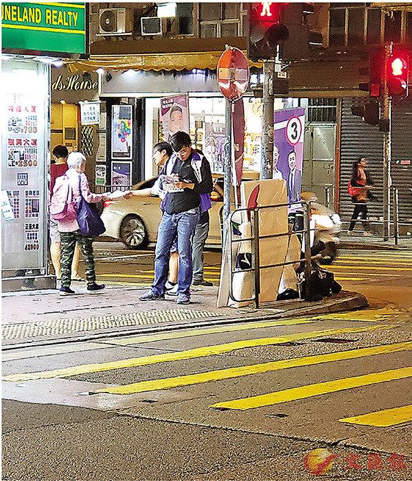 ■彭家浩義工成員在街站時態度懶散,大多都只顧聊天和看手機。 香港文匯報記者  攝