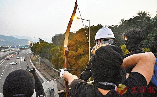 ■中大計劃在大埔第39區增建的大樓,或會威脅旁邊的東鐵線安全。圖為早前暴徒在中大用箭瞄準吐露港公路上的車輛。 資料圖片