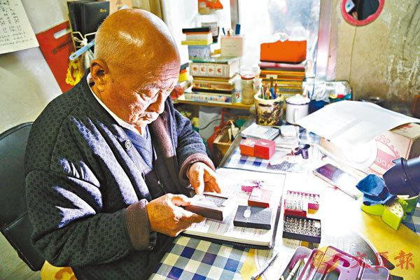 ■陳金元在整理他的米雕作品。