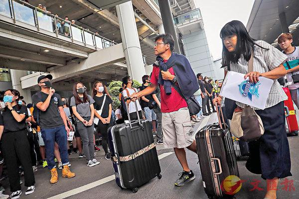 ■持續近半年的暴力示威嚇怕旅客不敢來港。圖為9月時兩名旅客在香港機場遇上激進示威者。 資料圖片