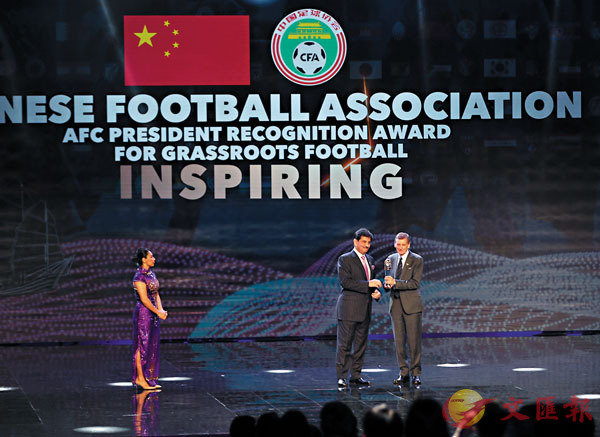 ■中國足協獲草根足球激勵獎,亞足協代表(右)代領獎。 香港文匯報記者黎永淦  攝