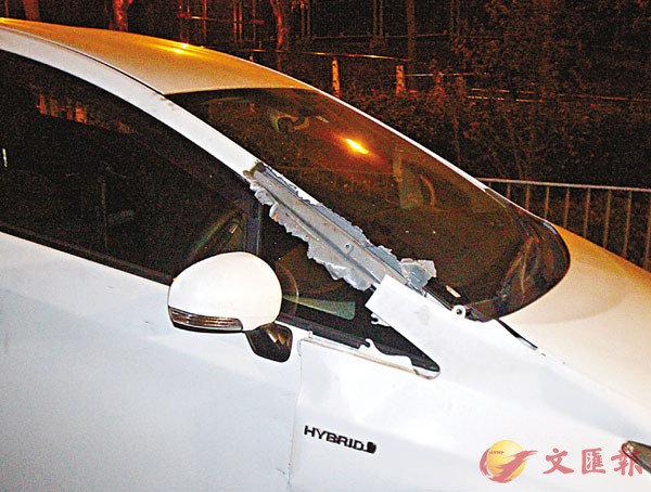 ■涉案白色私家車右邊金屬框留下一個子彈孔。 香港文匯報記者  攝