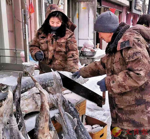 ■魚市商家用鋸把魚分割。 香港文匯報記者于海江 攝