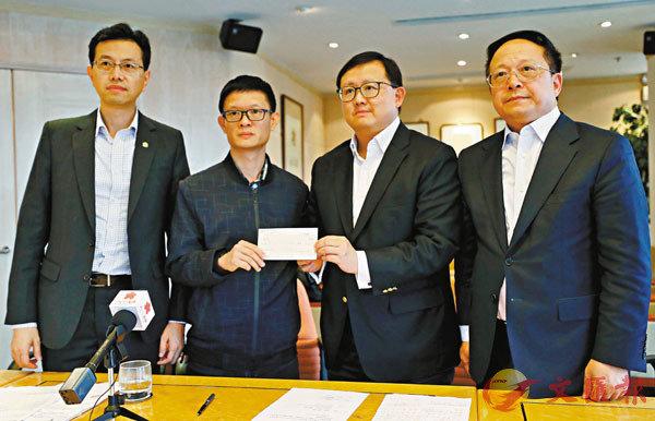 ■羅伯長子(左二)接收善款。 香港文匯報記者  攝