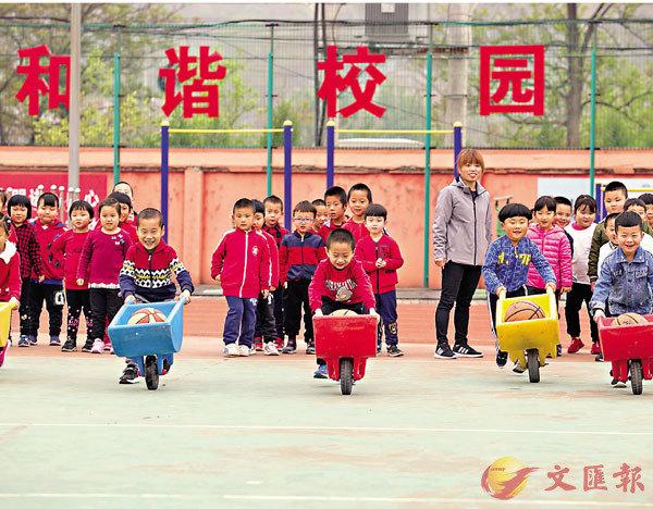 ■ 2019年,北京落實第三期學前教育行動計劃,新增幼兒學位3萬個。圖為北京一幼兒園的小朋友們參加小推車比賽。 資料圖片