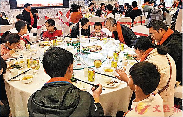 ■20戶外來工家庭在廣州共同享用豐盛的粵式團年飯。 香港文匯報 記者 敖敏輝 攝