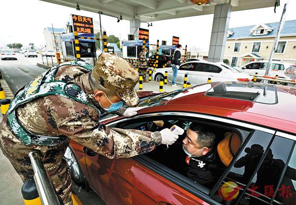 ■民兵為駕駛員檢測體溫。 美聯社