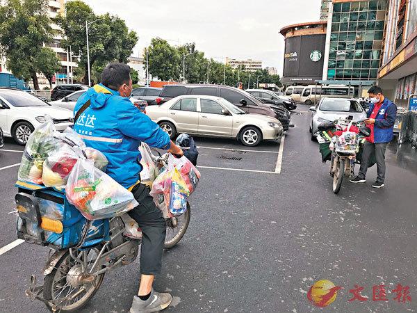 ■劉捷(左)和同事裝點好貨物準備去配送。 香港文匯報記者敖敏輝  攝