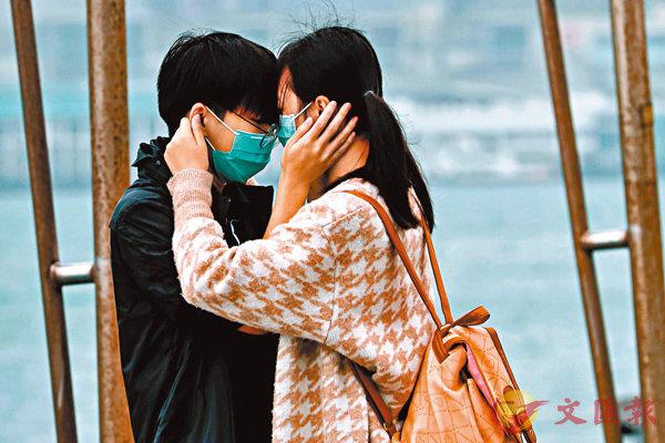 ■香港疫情還在發展中,一對情侶在情人節戴�茪f罩親熱。 路透社