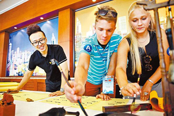 ■王官升在紀念中俄建交70周年交流活動上指導俄羅斯青年書法。 受訪者供圖
