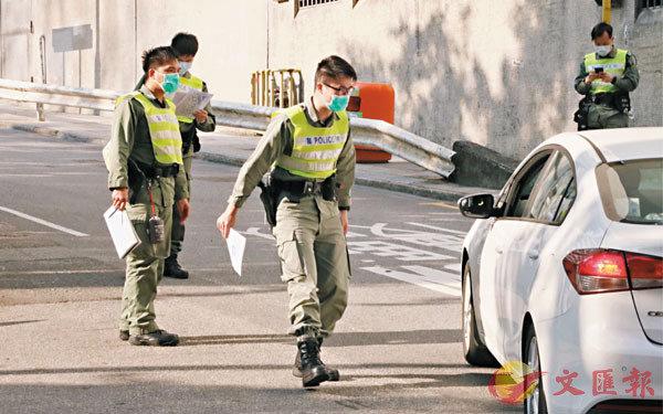 ■警方抗疫專隊向進入駿洋�h檢疫中心的車輛進行檢查。 香港文匯報記者  攝