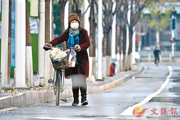 ■1月26日,在武漢街頭,市民佩戴口罩出行。 資料圖片