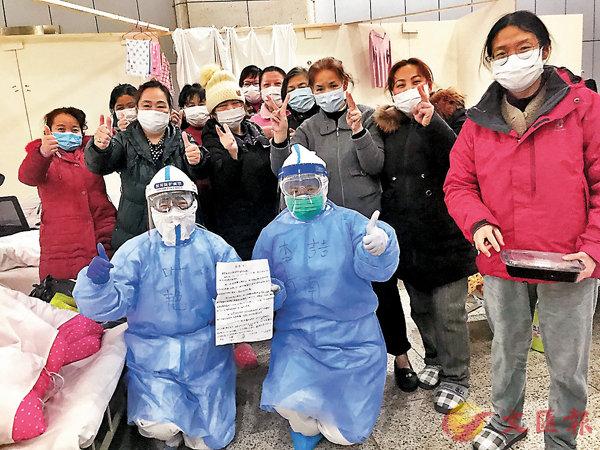 ■ 李�F(前排左二)同江漢方艙醫院的隔離患者相處得十分融洽。 受訪者供圖