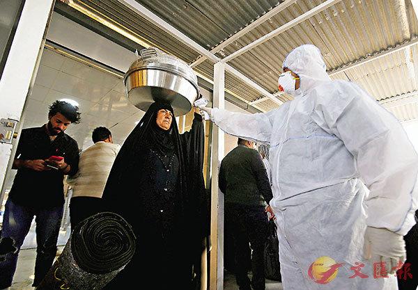 ■伊朗醫護人員為居民量度體溫。  路透社