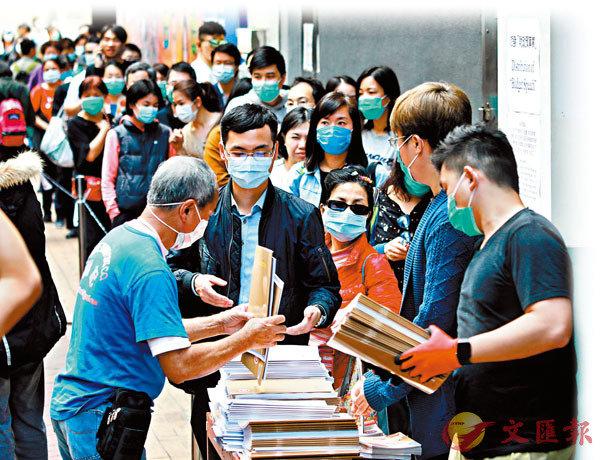 新年度財政預算案宣佈,將向年滿18歲的香港永久居民每人派發現金1萬元。圖為市民排隊領取新財政預算案報告書。   香港文匯報記者  攝