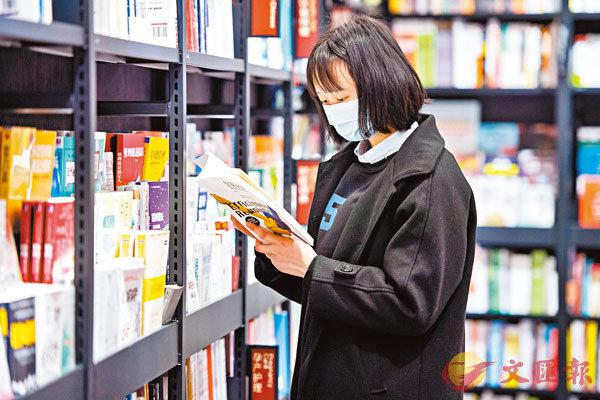■疫情肆虐下,實體書店遭受重擊,紛紛利用「雲端」自救。圖為長沙天心區西西弗書店,一名戴口罩的讀者在閱讀書籍。  新華社