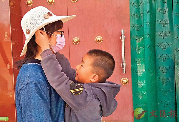 ■  出工前,苗薇的孩子為她佩戴口罩。 受訪者供圖