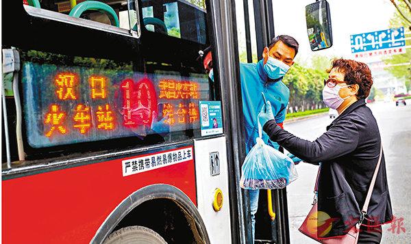 實名登記  ■武漢部分公交線路昨日恢復運營,圖為一名公交安全員指導乘客用手機掃碼實名登記上車。  中新社