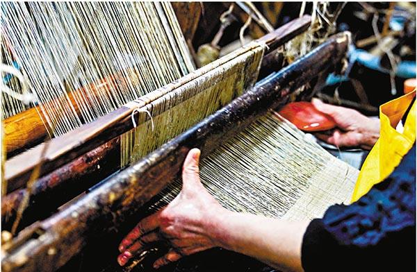 ■夏布小鎮的生產車間內,本地織女在織布機上工作。