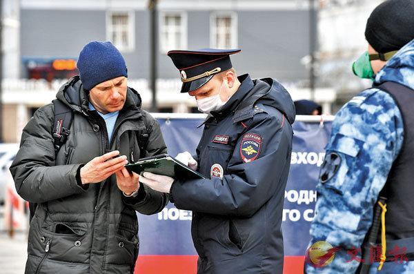 ■在莫斯科市及莫斯科州範围内出行必须申请电子通行证,但申请太容易,导致逾300万人出行。图为警察在莫斯科检查一名男子的通行证。  新华社