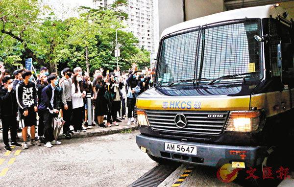 ■兩名謀殺案被告坐囚車離開法院,竟有青少年高舉黑暴手勢聲援。 香港文匯報記者  攝