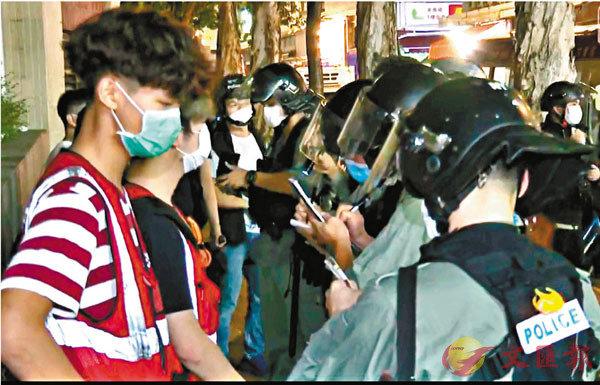 防暴警於又新街截查涉嫌違反「限聚令」的人, 並記錄他們的個人資料。
