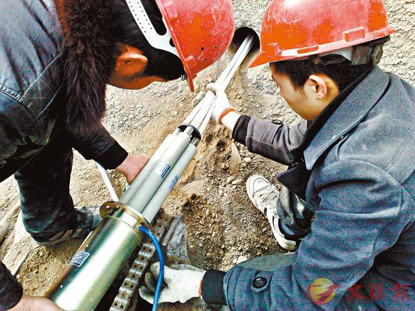■正在蘭渝鐵路邊坡安裝的「基建雲安」監測系統。記者李兵  攝